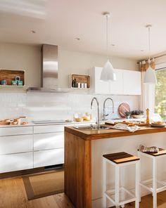 cocina blanca con parquet y alfombra e isla con sobre de madera taburetes y