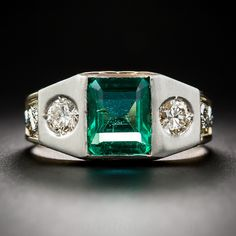 Vintage Emerald and Diamond Gent's Ring. A clean and crystalline, light to medium Mediterranean green emerald-cut emerald, weighing 2.15 carats, is set flush in a beveled platinum top and is highlighted on each side by a sparkling European-cut diamond. The main body of the ring is masterfully rendered in rich 18 karat gold and ornamented with platinum serpents overlaid on the shoulders and hand-engraved laurel leaves on the sides.