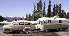 repainted airstream being pulled by a vintage suburban