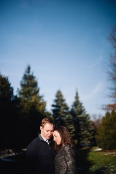 Bride and Groom pose in front of a blue sky and pine trees at Hartwood Acres Mansion in Pittsburgh, PA