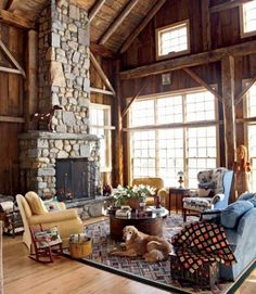 With the right touches, a converted barn makes for a warm common area. Here, a roaring fire in a hearth crafted from local fieldstones makes the living room a natural destination for family gatherings. High ceilings and expansive windows welcome plenty of light and offer architectural interest. Non-uniform seating, outdoor lamps, a crisscross patterned area rug and woodland-inspired items like the sculpted bear and horse figurines shown help make this