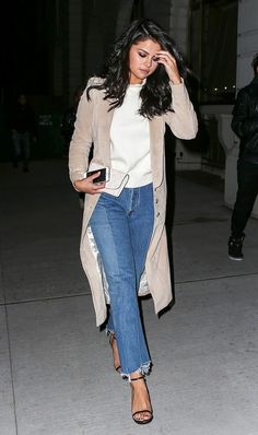 Selena Gomez tosses a chic trench coat over basic cropped flares, a mock neck top, and black ankle strap heels.