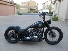 Flat black Softail custom with black rims and fork covers