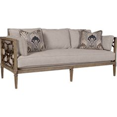Featuring a wood frame with striking openwork sides, this rustic sofa is perfect anchored by an ikat rug in the living room or parlor.