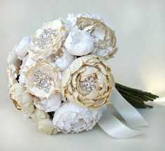 This silk fabric bridal bouquet is comprised of hand cut and formed silk fabric flowers of various shades of cream, off white and ivory. Each flower has its own hand placed highlights featuring either rhinestones, crystals or genuine freshwater pearls. Completely handmade and stunning!Measures about 9 1/2 inches (about 24 centimeters) in diameter and 11 inches long.Takes many hours to complete this beauty.Each flower is its own individual piece with a green dupioni silk ...