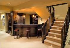 """Found this round mahogany bar and lit stairs on a list called """"10 ways to update your home on a budget."""" I think that they meant a really BIG budget."""