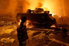 28 January 2011: A protester watches an Egyptian Army armoured vehicle burn in Cairo after President Hosni Mubarak ordered troops into Egyptian cities in an attempt to quell growing mass protests demanding an end to his 30-year rule