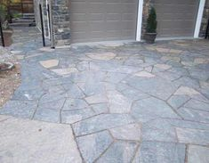 Landscaping driveways with natural stone is one of the most appealing ways to increase curb appeal. This beautiful flagstone driveway and front walkway also compliment the stonework of the walls and pillars of this garage.
