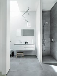 The family shares one main bathroom, which is outfitted with Vipp's new line of products: 982 bath furniture, a 906 faucet, and a 992 mirror. The shower sports a Raindance Connect showerhead by Hansgrohe, and there is a wall-mounted toilet by Villeroy & Boch. The Nomad light fixture is from Modular Lighting Instruments, and the floors are topped with ceramic tiles by LaFaenza.