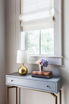 A stunning gray foyer console table sat on gold legs is topped with a beautiful gold leaf lamp sat under a window dressed in a white and light gray printed roman shade.