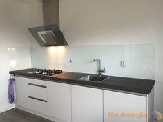 Deze witte greeploze keuken in Ede is verfraaid met een witte keukenwand van glas. Hieronder de keuken in Ede voor de…