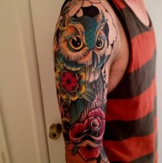 Funny cartoon like colored owl with flowers tattoo on sleeve