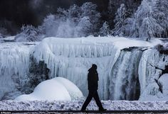 Icy: A man is pictured walking in front of the partially frozen American side of the Falls as subfreezing temperatures freeze the Northeast