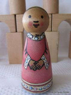 This is a hand painted wood folk tale style peg doll girl. This princess wears a lovely pink gown with edging of silver-gold set about with opals. She has a pale aqua cloak. This 3.5 tall wood peg doll has been detailed with archival pigmented ink and then hand painted with