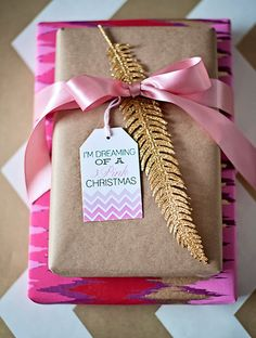 wrapping inspiration: chevron tags by Paiges of Style + gold glittered feather + kraft + modern pink-red-gold-purple zig zag wrap from Paper Source
