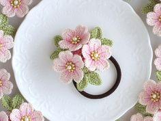 【作品の特徴】かぎ針編みの桜の花3輪にヘアゴムをつけました。花びらは編んだ後に1つずつ中央を染め、パールビーズをあしらい豪華な印象に仕上げました。花びらの形を保つためにテグスを編み込んでいます。あまり強い力が加わりますと花びらが変形する場合がございます。...