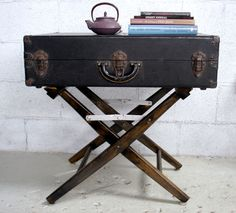 Side table created from a vintage suitcase and the legs of a director's folding chair. Originally from an Oakland, CA shop called Fernseed.