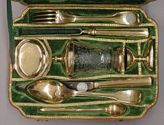 Travelling Set with Glass Beaker In Case, Samuel Bardet 1777/79, German (Augsburg) Gilt silver, steel, and glass;dyed and gold-tooled leather, velvet. Containing cutlery (serving fork and spoon, carving fork and knife, and a marrow spoon), a spice box, an egg cup, & a covered beaker, such luxury traveling sets in protective leather cases were a staple of Augsburg silversmiths. The beaker is engraved with a hunter & a huntress, suggesting this traveling set was intended for the hunting…