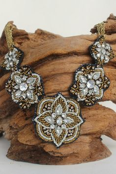 Make a statement with this gorgeous embroidered seed bead bib necklace!  White and gold beads are accented with faceted crystals on a black felted backing for a showstopping effect.
