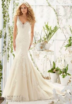 This sleeveless Mori Lee 2803 fit and flare wedding dress features crystal beading on the shoulder straps and edging the V-neckline and deep scoop back. This gown is styled in soft net over satin, embellished with Alencon lace appliques. Covered buttons accent the back of the gown and the skirt flows into a chapel train.