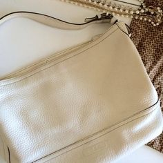 coach / leather purse ➳ coach ➳ 100% authentic ➳ white pebbled leather  ➳ monogram lining  ➳ 2 small pockets, 1 zip ➳ dimensions: 15'' x 10'' x 6''  ❥ worn with love. some sign of wear on front but not extremely noticeable. mark on back of purse, pointed out. soft leather that carries great form. Coach Bags
