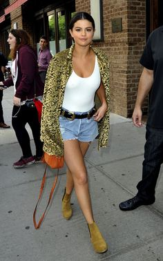 Selena Gomez wears a white bodysuit, cutoffs, a belt with metallic details, a gold and black blazer, an orange Gucci mini bag, and tan suede ankle boots