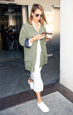 Jessica Alba wears a military-inspired jacket, mini dress, sneakers, and clear-frame sunglasses