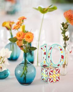 Etsy artisan Molly Caskey painted these ornate table numbers that were placed with small bud vases holding sturdy and tropical flowers