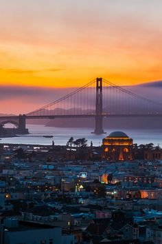 A stunning sunset view of an illuminated Palace of Fine Arts and the fog-shrouded Golden Gate Bridge.