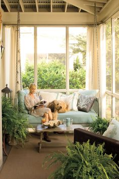 The back porch is outfitted with coral-patterned pillows and a swinging daybed to make a comfy retreat. Instead of shutters, the couple relies on durable draperies made from waterproof sailcloth for shade and privacy. Potted ferns add the lushness of nearby marshlands.