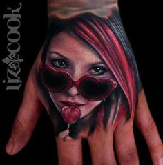 Pretty cool colorful tattoo idea. A girl with heart shaped sunglasses and red hair,  licking a heart lollipop. I love the minimal colors, but still colorful. Cool hand placement.-BirdY