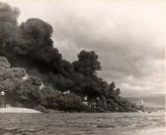 "View of ""Battleship Row"", probably taken on 8 December, the day after the Japanese raid, with USS Arizona still burning at right. In the center is USS West Virginia sunk alongside USS Tennessee The capsized USS Oklahoma is at left, alongside USS Maryland"
