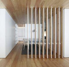 minimalistisches interior design in holz mit kücke weiß und dezente raumteilung durch drehebaren holzlamellen