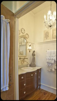 The Old Painted Cottage Unique Goods and Curious Finds - love the tall bead-board with picture rail and chandelier in the bathroom!