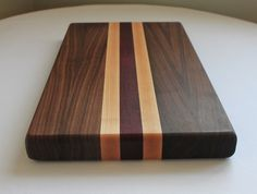 """This cutting board is built to last. It is made with Walnut, Maple and Purpleheart and its measurements are 17 1/"""" W x 11"""" H x 1 1/2"""" thick."""