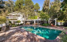 This charming home offers tranquility and city lights views with a sparkling pool and lush gardens. Tower Lane | Beverly Hills
