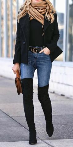 Helena Glazer + pair of striking thigh high boots + skinny denim jeans + statement belt + sexy + chic + winter style + oversized beige scarf + black cropped overcoat.   Brands not specified.