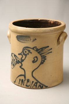 "STONEWARE CROCK WITH INDIAN. Second half 19th Century. Cobalt blue freehand profile of an American Indian with a mohawk. Labeled ""Indian"" below with a word balloon from the figure saying ""Hold Him"". Stamped label ""C.W. Braun, Buffalo, NY"". 10""d. 10 3/4""h. Sold for $23,500"