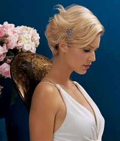 Brides: Tousled, Short Wedding Updo . Starting with an extreme side part—just north of the ear—hair is swept back in sections and ends are pinned under; a few fat curls hang freely. Straggling ends are anchored by jeweled hair combs placed just so. Perfect product: To build enough oomph for this tousled style, prep with Tresemmé Tres Extra Hold Mousse.