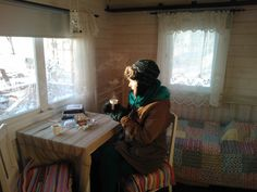Having a cup of coffee in the summer cabin in the middle of winter.