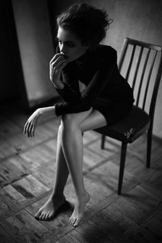 .Black and white photograph. Woman sitting on chair.