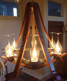 Beautiful use of barrel staves and wine glasses to make a unique light fixture.