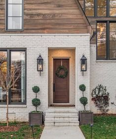 stunning material combination of wood and painted white brick, looks like just part of a modern home addition with lots of black framed windows