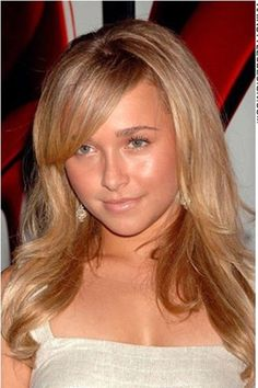 Hayden Panettiere has her hair styled long and straight. This celebrity looks sexy with her hair falling long down her back with long straight bangs brushed across at the eye. The hair has volume and it is a stylish look.Hayden's hair is cut long.The hair is coloured a rich and creamy light brown to blonde.