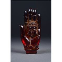 Chinese carved amber figure; featuring Buddha hand with overlapping lotus petals and Buddha inset in relief in the palm of the hand