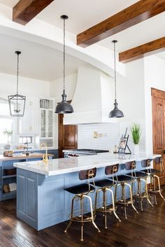 Blue modern farmhouse kitchen with rustic industrial elements like brass hardware, a white farmhouse sink, white subway tile, zinc pendant lights and a hanging iron lantern.
