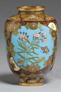 A Small Cloisonné Enamel Vase Meiji period (19th century), inscribed Kyoto Namikawa The small vase of compressed ovoid form designed with light blue oval panels containing butterflies and flowers worked in gold wire and polychrome enamels, the surrounding areas with scattered chrysanthemums on an aubergine ground, the shoulder and foot designed with floral lappets on a green or gold and black mottled ground; brass mounts; signature on silver tablet mounted on base
