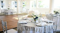 Silver table overlays. Elegant wedding reception. Diamond napkin rings. Blue orchid flowers. Silver chargers. Silver chiavari chairs