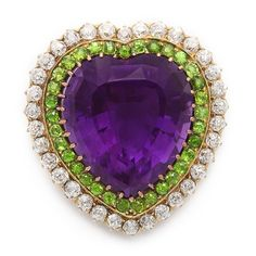 Amethyst, diamond, and demantoid garnet heart-shaped brooch, which can also be worn as a pendant.  Mounted in gold. English, ca. 1900. Purple (amethyst) is the royal color and emblematic of freedom and dignity; white (diamonds) represents purity; green (demantoid garnets) is the color of Spring and new beginnings.