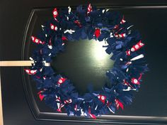 Coast Guard Deployment rag wreath, good for any branch of the military or any occasion, change the colors and ribbon to match your theme. The metal wreath frame was $4 from michael's, the blue cloth is 2 Coast Guard ODU blouses plus ribbon in 3 colors cut in the same length strips. USCG